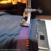 Using a sewing machine to sew a new zipper to a sleeping bag