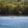 A canoe paddles on Canadice Lake below fall colors, New York